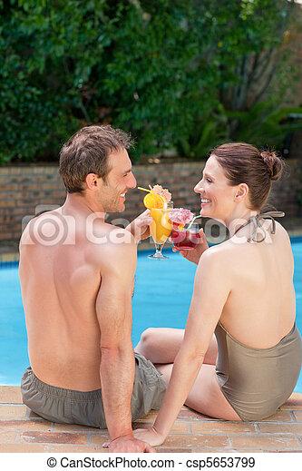 Una pareja feliz bebiendo cócteles y brindando entre sí - csp5653799