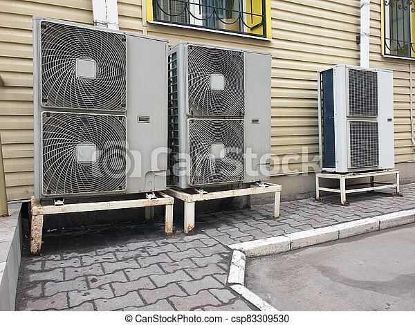 outdoor air conditioning units of office space attached to facade of building - csp83309530