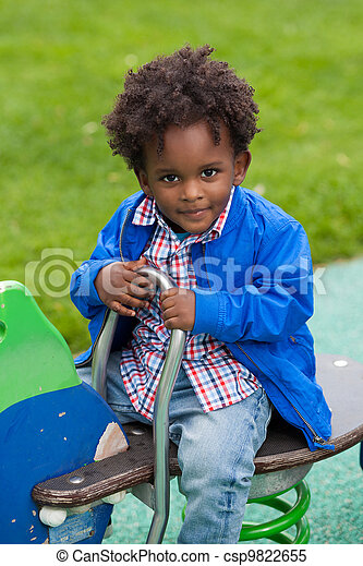 Outdoor portrait of a black baby playing at playground - csp9822655