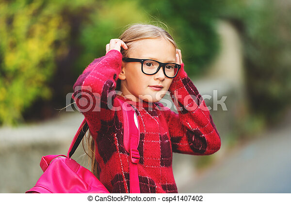 9a5416034f25 Outdoor portrait of a cute little 9 year old girl, wearing red pullover,  glasses