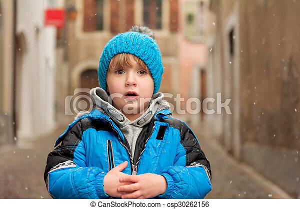 Outdoor portrait of a cute little boy in a city under snowfall, wearing warm blue jacket and knitted hat - csp30262156