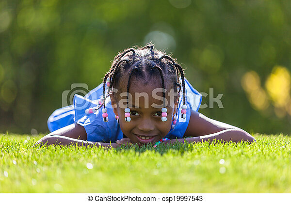 Young Teen Girl Lying On Green Grass And Reading Book