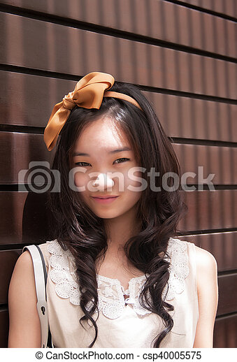 Outdoor portrait of attractive asian woman smiling - csp40005575