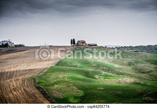 Overcast sky over a small hill in Tuscany - csp84255774