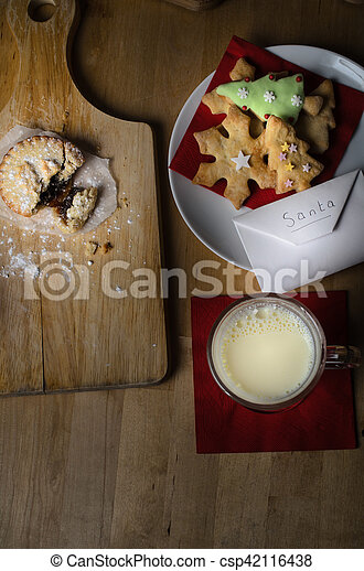 overhead shot on wooden table of biscuits cookies milk and mince pies left out on christmas eve for santa with list in envelope - Christmas Eve Snacks