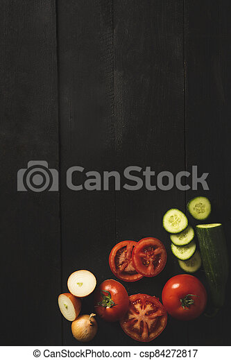 Overhead shot with vegetables on a black background - csp84272817