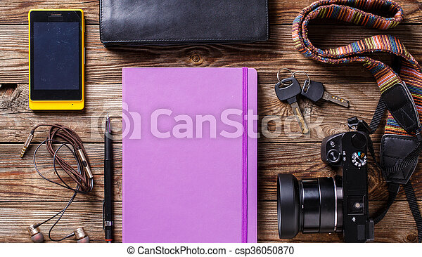 Overhead view of travel gear placed on wooden table. Mobile phone, earplugs, violet sketchbook, pencil, camera and purse. Flat lay top view. - csp36050870