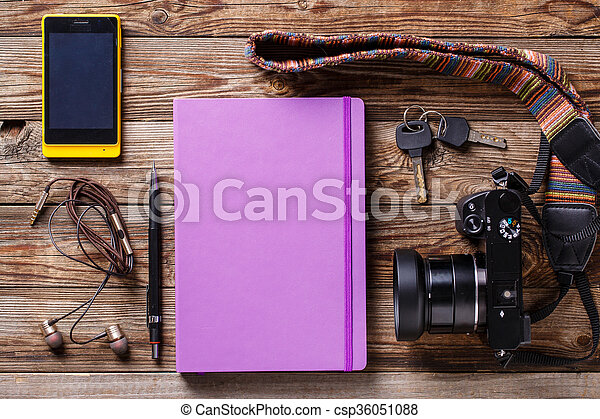 Overhead view of travel gear placed on wooden table. Mobile phone, earplugs, violet sketchbook, pencil, camera and purse. Flat lay top view. - csp36051088