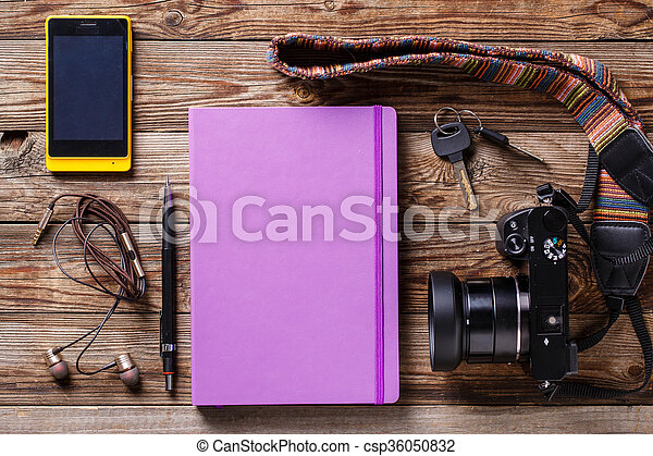 Overhead view of travel gear placed on wooden table. Mobile phone, earplugs, violet sketchbook, pencil, camera and purse. Flat lay top view. - csp36050832