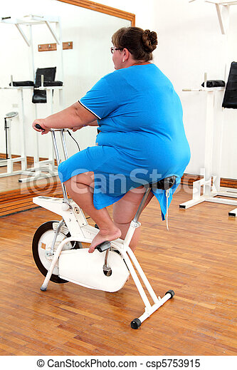 overweight woman exercising on bike - csp5753915