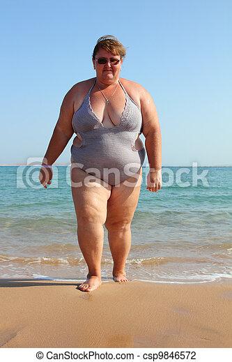 overweight woman on beach - csp9846572