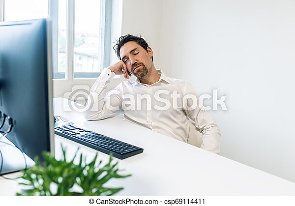Overworked young businessman sleeping at his desk - csp69114411