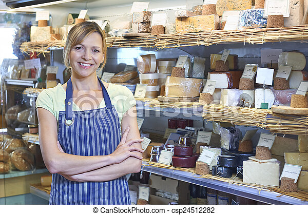 Owner Of Delicatessen Standing Next To Cheese Display - csp24512282