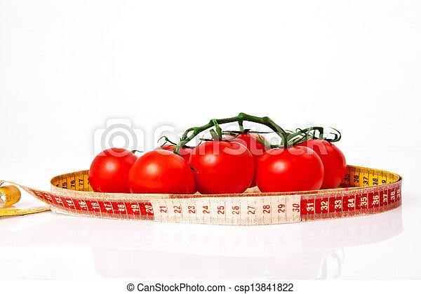 El concepto de pérdida de peso dietético con cinta mide tomates orgánicos - csp13841822