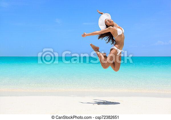 Feliz mujer de playa saltando de peso pierde éxito - csp72382651