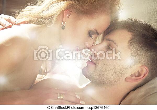 Ein sexy junges Paar, das sich küsst und im Bett spielt. - csp13676460