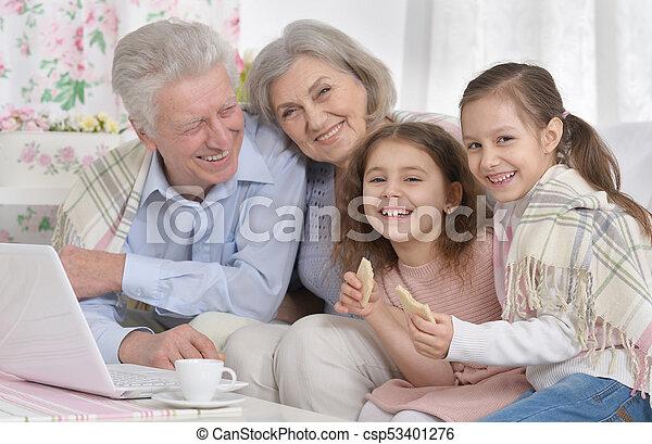 Happy Senior Paar mit Enkeln und Laptop - csp53401276