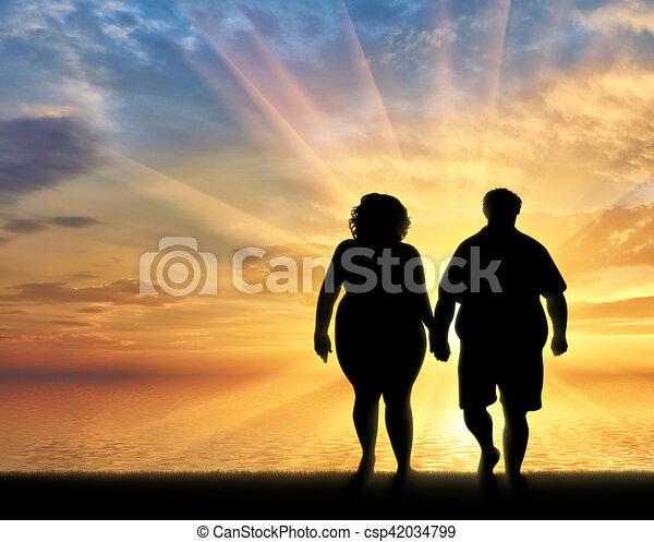Thermonuklearer sonnenuntergang. Silhouette von einem paar am strand sehen  einen romantischen sonnenuntergang.