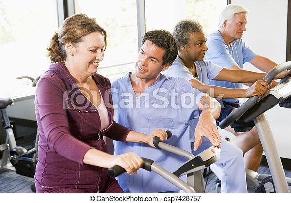 Enfermera con paciente en rehabilitación usando máquina de ejercicios - csp7428757