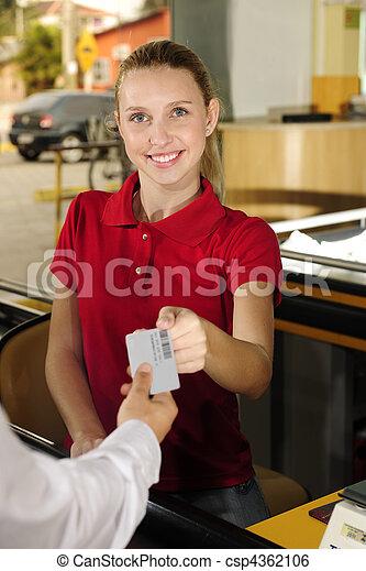 Una mujer que paga cajera en el mostrador - csp4362106