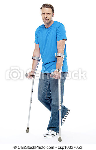 Painful expression by young man walking with help of crutches - csp10827052