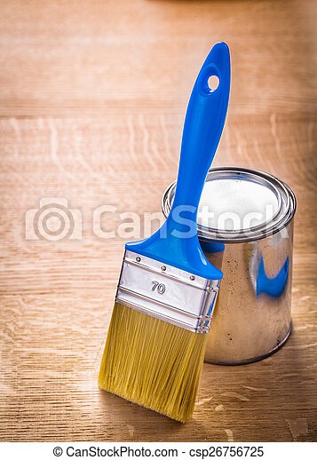 paint brush with blue handle standing near can on wooden board - csp26756725