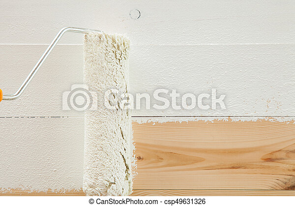 Paint roller brush with white paint on wooden background - csp49631326