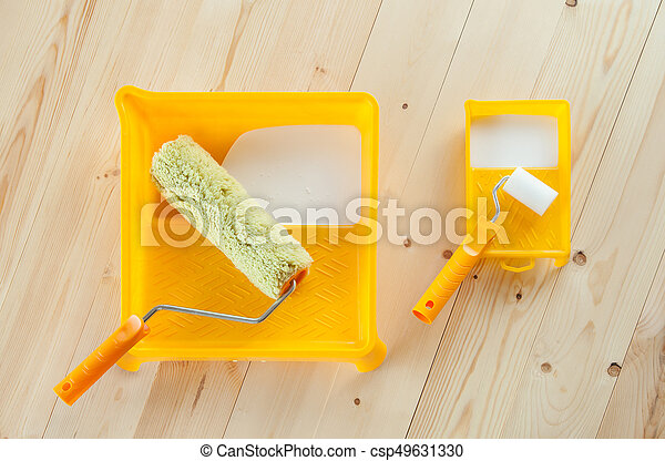 Paint roller brush with white paint on wooden background - csp49631330