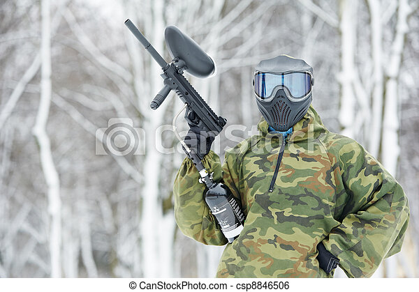paintball player with marker at winter outdoors - csp8846506