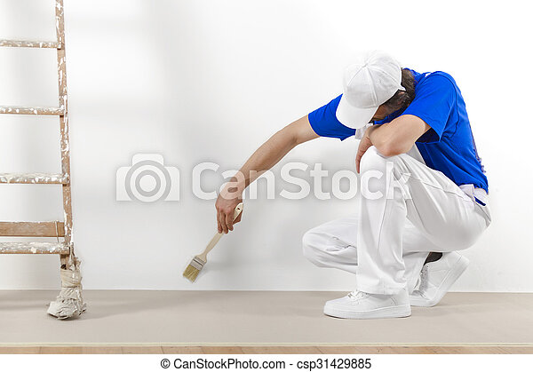 Painter man at work with brush painting a white wall.  - csp31429885