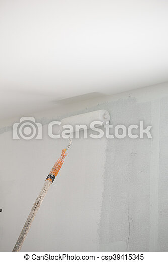 painting a wall with roller - csp39415345
