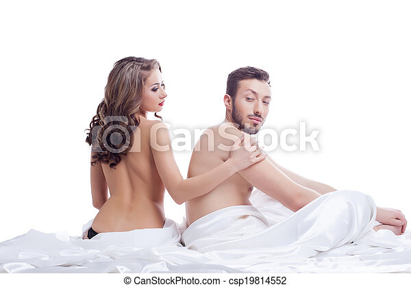 Pair of beautiful young lovers posing in bed - csp19814552