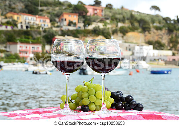 Pair of wineglasses and grapes against the harbour of Portvenere, Italy - csp10253653