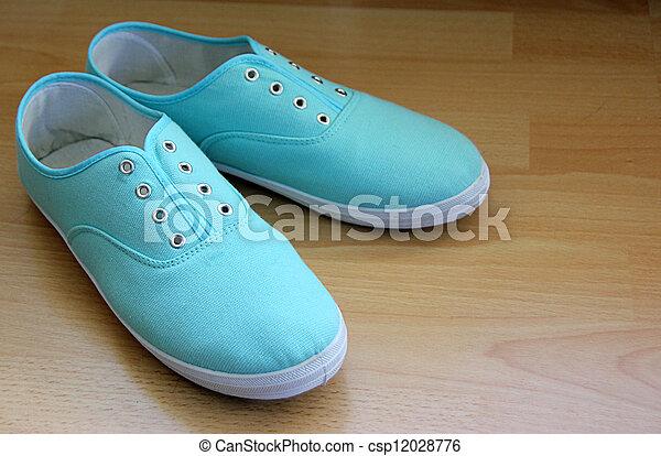 Pale blue canvas shoes without shoe laces.