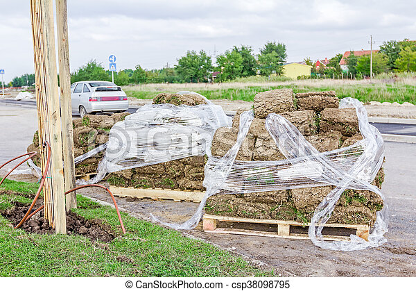 Pallet of sod rolls are wrapped in foil, unrolling grass