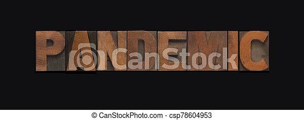 Pandemic word in wood type on black - csp78604953