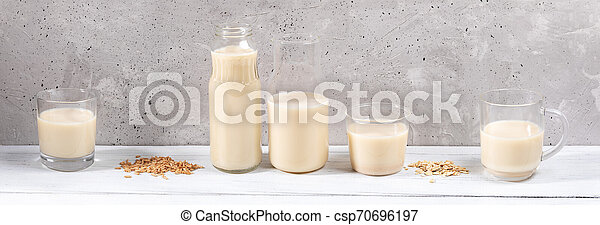 Panorama image of row of glass containers with oat milk on white wooden table on grey concrete wall background. - csp70696197