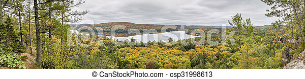 Panorama Looking Out Over a Lake Surrounded by Forest in Autumn  - csp31998613