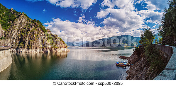 Panorama of a mountain lake Near the dam. Beautiful blue sky with clouds - csp50872895