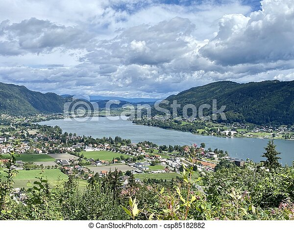 Panorama of Ossiacher Lake in Carinthia, Austria from high above on a summer day with great cloudscape - csp85182882