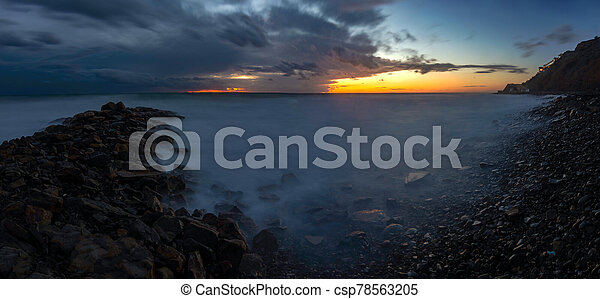 Panorama of three frames a general view of the rocky shore of the Black Sea coast after sunset, Anapa, Russia - csp78563205