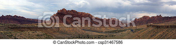 Panoramic of Road winds through Spotted Wolf Canyon with dramatic clouds in sky - csp31467586