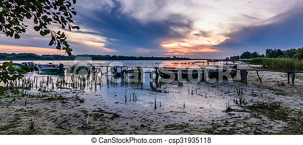 Panormic landscape with boats on the water near the old pier. Beautiful view of colorful sunset on the lake - csp31935118