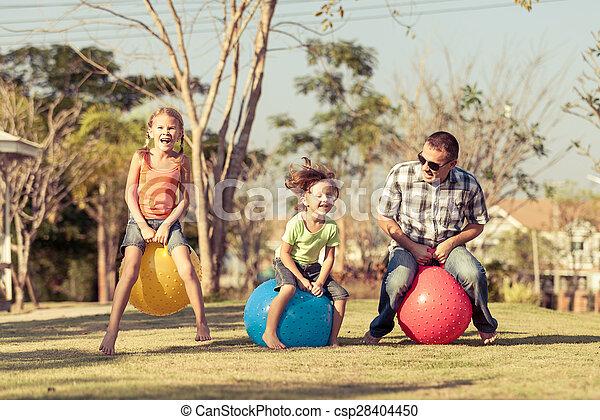 Papá y niños jugando en el césped - csp28404450