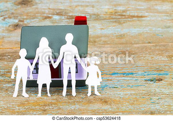 Silueta de papel de familia y casa en escritorio de madera. Un concepto de seguro - csp53624418