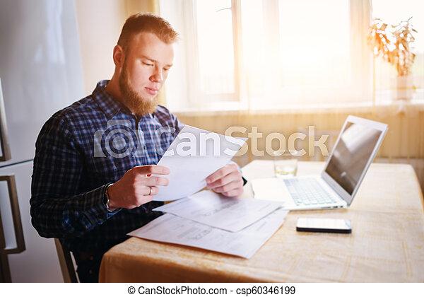 Hombre de negocios en casa, está trabajando con un portátil, revisando papeleo y facturas - csp60346199