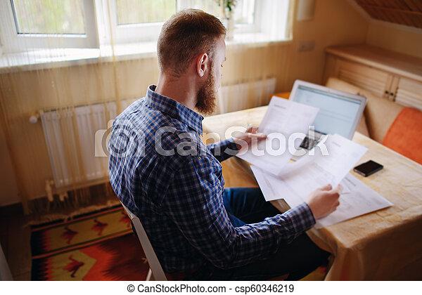 Hombre de negocios en casa, está trabajando con un portátil, revisando papeleo y facturas - csp60346219