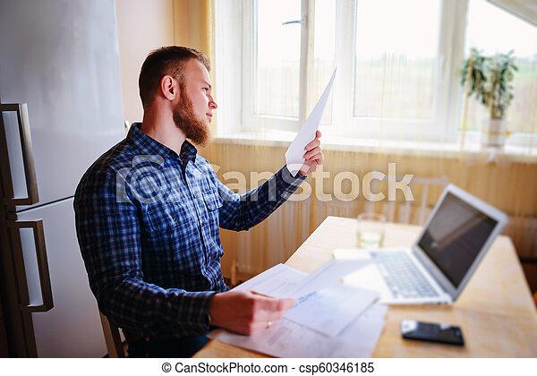 Hombre de negocios en casa, está trabajando con un portátil, revisando papeleo y facturas - csp60346185