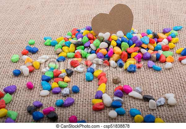 Paper heart amid pebbles on canvas ground - csp51838878