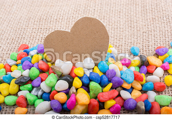Paper heart amid pebbles on canvas ground - csp52817717